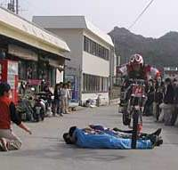Four willing and rather intoxicated men lie down on the road for some motorbike acrobatics.