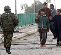 A member of the Japanese SDF contingent to Samawah in Iraq -- whose deployment Morita claims is 'unconstitutional' -- waves to local youths in January 2004. | AP PHOTO