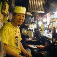 Tatsuo Takeuchi behind the wok at Sanyo Ramen in Yokohama, where meals are served up with generous side orders of humor. | ERIC PRIDEAUX PHOTOS