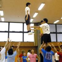 Shockers members practicing stunts in a gym (above and left) and performing in Waseda University events in 2006 and 2007 (below). | YOSHIAKI MIURA PHOTOS; PHOTOS COURTESY OF SHOCKERS