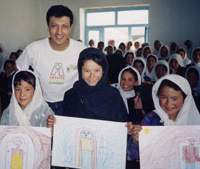 Ethnic Hazara girls with Hector Sierra in Bamyan, Afghanistan, display their renderings of 'My City' in May 2002, just a few months after the Taliban had left. Earlier, the girls had not been permitted to attend school or even to draw.  Earlier, the girls had not been permitted to attend school or even to draw. | PHOTO COURTESY OF ARTISTS WITHOUT BORDERS