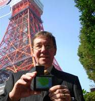 Sales Manager Colin Shea poses in front of Tokyo Tower with his company's patest product — a personal portable multilanguage navigation system.
