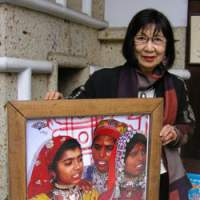 Hiroko Iwatate stands by a poster for an exhibition of her passion, Indian textiles.