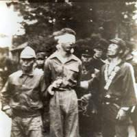 A survivor of the B-29 crew is led from the village hall after being captured and tortured   PHOTO COURTESY OF VAL BURATI/GEORGE McGRAW