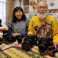 Out of Africa: Michio Hiraiwa and his daughter, Masayo, pose at their African photo and craft gallery in Tokyo's Suginami Ward. The duo have traveled to Kenya together nearly 140 times and taken a total of 3,700 Japanese tourists to the country.  | YOSHIAKI MIURA