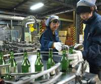 Workers collect newly bottled sake from the production line at a Kyoto brewery (above); 72-liter sake kegs adorn another brewery's entrance (below). | AP PHOTO