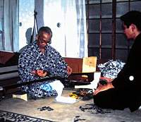 The late Tsuruzawa Enza V teaching Tsuruzawa Enza VI -- Tsuruzawa Enjiro at the time -- the intracacies of playing the shamisen