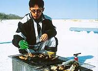 Nemuro's ecotourism promotion bureau grills fish during a trek over the frozen lake.
