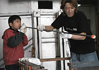 A kid tries his hand at glass-blowing.