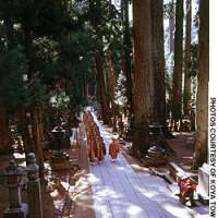 Monks tread a path through Okunoin Temple on Mount Koya.