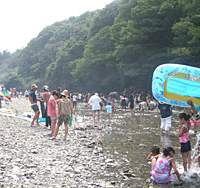 River lovers pour onto the Akigawa's bank; a sign says that if you hear a siren or speaker, the water level will rise and you'd better hit the shore fast.