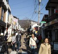 Visitors throng Kyukaruizawa shopping street, where crafts and local fare abound.