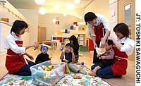 Toddlers play with staff at a nursery run by the cosmetics firm Shiseido Co. in Tokyo's Shiodome business district.