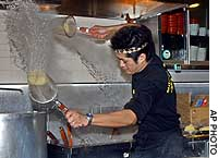 Ramen chef Konosuke Takewaka whips an acorn-shaped sieve of noodles through the air in a figure-eight pattern at Shiodome ramen restaurant in Tokyo in this file photo from February 2004.