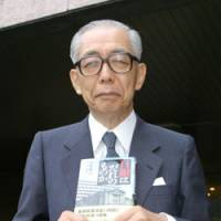 Nobuyuki Nakahara, a former member of the Bank of Japan Policy Board, poses last month in Tokyo with his book 'Who Does the BOJ Belong To?' | TETSUSHI KAJIMOTO PHOTO