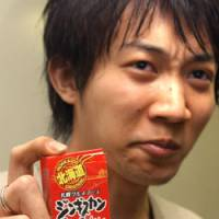 Graduate student Noriyuki Suzuki is unimpressed with the taste of Genghis Khan caramels manufactured by Sapporo Gourmet Foods Co. | SATOKO KAWASAKI PHOTO