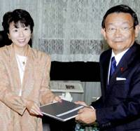 New Economic and Fiscal Policy Minister Hiroko Ota receives notes from her predecessor, Kaoru Yosano, in her new office in Tokyo's Kasumigaseki district Wednesday. | KYODO PHOTO