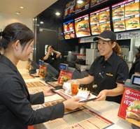 A Burger King worker at the Shinjuku outlet in Tokyo serves a member of the media Wednesday at a media preview. The outlet opens to the public Friday. | YOSHIAKI MIURA PHOTO