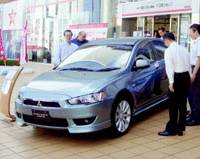 Pedestrians check out Mitsubishi Motors Corp.'s sporty new Gallant Fortis sedan in front of the carmaker's headquarters in Minato Ward, Tokyo, last week.   KYODO PHOTO