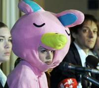 A Nova Corp. teacher clad like the firm's pink rabbit mascot faces reporters Thursday with union reps Louis Carlet (center) and Bob Tench at the Foreign Correspondents' Club of Japan in Tokyo. | AP PHOTO