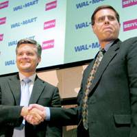 Brett Biggs (left), senior vice president of Wal-Mart Stores, Inc., and Edward Kolodzieski, chief executive officer of Seiyu Co., Ltd., celebrate Seiyu's becoming a wholly owned Wal-Mart subsidiary, at the Tokyo Stock Exchange on Oct. 22. | KYODO PHOTO