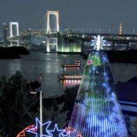 Visitors to Tokyo's Odaiba take a photo in front of Christmas illuminations. | KYODO PHOTO