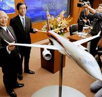 Flying high: Mitsubishi Heavy Industries Ltd. Chairman Kazuo Tsukuda (left) smiles during a news conference in Tokyo in March to announce that the Mitsubishi Regional Jet would go into commercial production. | KYODO PHOTO