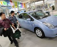 Fewer buyers: Visitors to a Toyota Motor Corp. showroom in Tokyo eyeball a Prius hybrid last week. Toyota on Monday revised its 2008 global sales target downward to 9.5 million units. | AP PHOTO