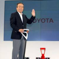 Winging it: Toyota Motor Corp. Executive Vice President Takeshi Uchiyamada demonstrates the Winglet personal transportation vehicle in Tokyo on Friday. | YOSHIAKI MIURA PHOTO