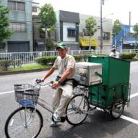 Making the rounds: Yusuke Sakurai, an employee of a Yamato Transport Co. service center in Koto Ward, Tokyo, uses an electric bicycle to deliver parcels on Aug. 4. | HIROKO NAKATA PHOTO