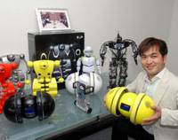 On a roll: Robotics company ZMP Inc.'s founder and chief executive Hisashi Taniguchi holds a miuro rolling music player in an office in Meguro Ward, Tokyo. Other products, including the nuvo and e-nuvo, are on the table. | YOSHIAKI MIURA PHOTO