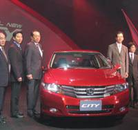 Car culture: Fumihiko Ike (third from right) and other Honda executives introduce the City at a news conference in Bangkok in September. At right, a Bangkok street is jammed with traffic during evening rush hour. | HIROKO NAKATA PHOTO