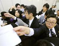 Hold the press: Employees of listed companies rush to put their earnings reports into shelves for news releases at the Tokyo Stock Exchange's press club on Oct. 31. | KYODO PHOTO
