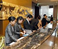 Check it out: Receptionists at Shangri-La Hotel, Tokyo work the front desk during a media preview last week. The lacquered and gilded carving behind them is just one of the many Chinese artworks decorating the hotel. | YOSHIAKI MIURA PHOTO