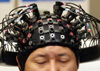 Mind-meld: A Honda employee uses headgear to demonstrate technology that links human thoughts to robots at the automaker's headquarters in Tokyo. | AP PHOTO