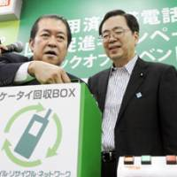 Insert here: Internal Affairs and Communications Minister Kunio Hatoyama (left) and Environment Minister Tetsuo Saito show off a mobile phone collection box in Tokyo Wednesday. | KYODO PHOTO