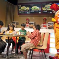 Going wireless: Children try to connect their Nintendo DS consoles to a wireless Internet service at a McDonald's outlet in the Tokyo Midtown shopping complex during a demonstration for the media Sunday. | HIROKO NAKATA PHOTO