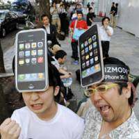 Fans of the iPhone, Apple Inc.'s touch-screen cell phone, wear paper mockups of the smart phone Friday in Tokyo. At the Omotesando district flagship store, 200 people lined up for the product's Japan debut. | KYODO PHOTO