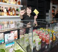 Test market: A clerk at Lcafe, which opens Wednesday in Tokyo's Shibuya district, holds a token that can be exchanged for sample products from various companies. The tokens are given out with food and drink purchases. | YOSHIAKI MIURA PHOTO