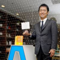 Head coach: Yoshiyuki Suzuki, president of Coach A Co., holds one of his books on corporate coaching while standing in front of his office in Chiyoda Ward, Tokyo, last month. | YOSHIAKI MIURA PHOTO