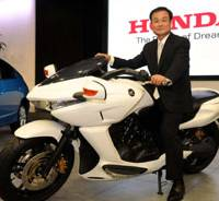Mean machine: Takanobu Ito, president of Honda Motor Co., displays one of the company's motorbikes Monday at the firm's headquarters in Tokyo. | SATOKO KAWASAKI PHOTO