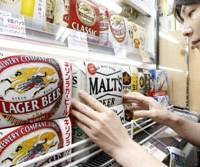 Pop its cap: Beers from Kirin Brewery Co., Suntory Liquors Ltd. and other companies line shelves at a liquor store in Osaka on July 13. | KYODO PHOTO