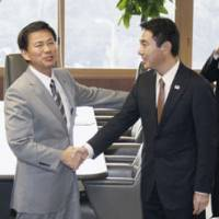 Narita or bust: Chiba Gov. Kensaku Morita gestures grandly before entering talks Wednesday with transport minister Seiji Maehara at the transport ministry. | KYODO PHOTO