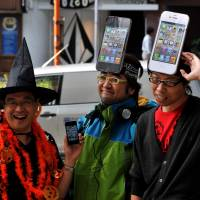 Dialed in: People line up with hats modeled after the new iPhone 4S handset in front of Softbank's flagship shop in Tokyo's Omotesando district Friday morning. | YOSHIAKI MIURA