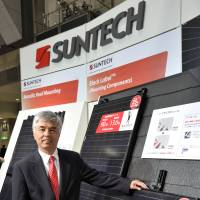 Place in the sun: Yutaka Yamamoto, president of Suntech Power Japan Corp., stands in front of the firm's solar cell exhibit at Tokyo Big Sight in March. | YOSHIAKI MIURA