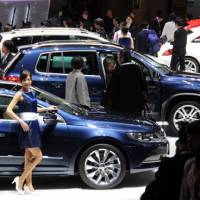 A model poses in front of a car during Wednesday's media preview at the Tokyo Motor Show in Tokyo Big Sight in Koto Ward. | SATOKO KAWASAKI