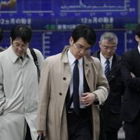 Downcast: Pedestrians cross an intersection in central Tokyo last week. The Bank of Japan's 'tankan' survey released Thursday indicates confidence at major manufacturers fell over the last quarter.   AP PHOTO