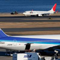 Business as usual: An All Nippon Airways Co. jet parks at  Haneda airport in Tokyo, while a Japan Airlines Co. flight taxis  on Wednesday.  | AP