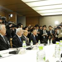 Power point: Prime Minister Shinzo Abe (right) meets with business leaders Tuesday at his office. | KYODO