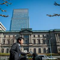Wheeling and dealing: A man cycles past the Bank of Japan on Wednesday. The economy unexpectedly shrank last quarter as falling exports and a business investment slump outweighed improved consumption. | BLOOMBERG